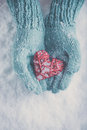 Woman Hands In Light Teal Knitted Mittens Are Holding Beautiful Glossy Red Heart On Snow Background. Love, St. Valentine Concept Stock Images - 61533184