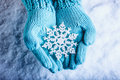 Female Hands In Light Teal Knitted Mittens With Sparkling Wonderful Snowflake On A White Snow Background. Winter Christmas Concept Royalty Free Stock Photos - 61552198