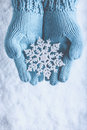 Female Hands In Light Teal Knitted Mittens With Sparkling Wonderful Snowflake On Snow Background. Winter And Christmas Concept Royalty Free Stock Photo - 61571535