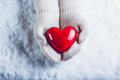 Female Hands In White Knitted Mittens With A Glossy Red Heart On A Snow Background. Love And St. Valentine Concept. Royalty Free Stock Image - 61571756