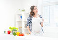 Beautiful Pregnant Smiling Woman In The Kitchen Eating Fruits Stock Photo - 61602090