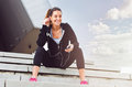 Young Woman Taking A Break From Exercising Outside With Cellphone Stock Image - 61711151