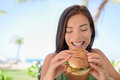 Happy Woman Eating Burger Sandwich At Beach Royalty Free Stock Images - 61717139