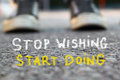 Low Angle Image Of Asphalt Road And Person Sneakers With The Text Stop Wishing Start Doing Royalty Free Stock Photography - 61786687