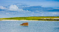 Old Rusted Sunken Boat  And Eolic Fan In Background Royalty Free Stock Photography - 61805677