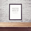 Poster Mock Up Template With Wooden Table Over Brick White Wall Royalty Free Stock Images - 62002419