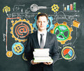 Man Holding A Pack Of Books With Blackboard With Busines Royalty Free Stock Photography - 62010197