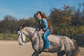 Pretty Girl Riding Her Grey Horse Royalty Free Stock Photography - 62163767