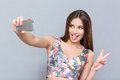 Beautiful Young Woman Making Selfie And Showing Tongue Royalty Free Stock Image - 62196306