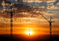 Hoisting Cranes Working On Beautiful Cloudy Sky With Orange Sunset Royalty Free Stock Photography - 62283627