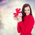 Composite Image Of Smiling Brunette In Red Jumper Hat Showing A Gift Royalty Free Stock Image - 62288656