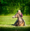 Woman With Long Blond Hair Sitting On Lying Horse And Smiling Royalty Free Stock Photography - 62305977