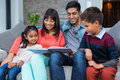 Happy Young Family Reading A Book Together Stock Photography - 62326192