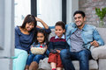 Happy Young Family Eating Popcorn While Watching Tv Stock Photography - 62326212