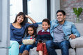 Happy Young Family Eating Popcorn While Watching Tv Royalty Free Stock Photo - 62326215