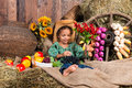 Little African Girl In Cowboy Hat Sitting On Straw Bag With Fruits Royalty Free Stock Photography - 62413197