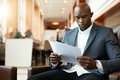 Businessman Sitting In Hotel Lobby Using Cell Phone And Laptop Stock Image - 62445431