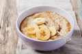 Bowl Of Oatmeal Porridge With Banana And Caramel Sauce On Rustic Table, Hot And Healthy Breakfast Royalty Free Stock Image - 62536646
