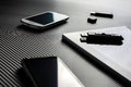 2 Business Mobiles With Reflections And An USB Drive Lying Next To A Blank Tablet With USB Drive On Top, All Above A Carbon Layer Royalty Free Stock Images - 62661879