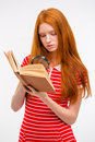 Concentrated Redhead Young Female Reading Book Using Magnifier Glass Stock Photos - 62752173