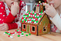 Little Adorable Girls Decorating Gingerbread House Stock Image - 62818591