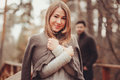 Young Woman In Cozy Warm Cardigan Walking Outdoor In Autumn Forest, With Boyfriend On Background Royalty Free Stock Image - 62834126