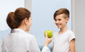 Doctor With Green Apple And Happy Boy In Clinic Royalty Free Stock Photography - 62848587