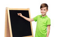 Happy Boy With Chalk And Blank School Blackboard Stock Photo - 62889500