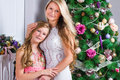Happy Young Woman With Cute Teen Daughter Near The Christmas Tre Stock Images - 62923094