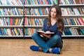 Smiling Young Girl  Sitting On The Floor In The Library Reading Stock Photos - 62975023