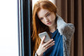 Attractive Lady  Standing Near The Window With Cellphone Royalty Free Stock Photos - 63050578