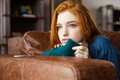 Pretty Pensive Redhead Girl Lying On Sofa And Thinking Stock Image - 63050651