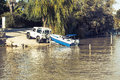 All Terrain Vehicle Towing A Trailer With A Boat On Top Into The River. Stock Image - 63119471