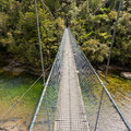 Swing Bridge Over Green Jungle River New Zealand Royalty Free Stock Images - 63203139