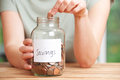 Woman Putting Coin Into Jar Labelled Savings Stock Photo - 63215680