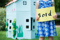 Little Girl Holding Sold Sign Outside Cardboard Playhouse Royalty Free Stock Image - 63227566