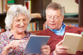 Senior Couple Using Digital Tablet And Reading Book Royalty Free Stock Image - 63256356