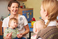 Two Mothers With Children Chatting At Playgroup Stock Image - 63266231
