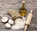 Wheat Flour In A Canvas Bag, The Olive Oil In A Glass Carafe, A Large Salt Shaker Wood, Raw Eggs, A Wooden Rolling Pin: Set For Ma Stock Photo - 63385010
