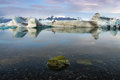 Reflection Of Ice Cubes With Moss Rock Foreground At  Jokulsarlon Glacier Lagoon Royalty Free Stock Image - 63453746
