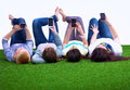 Four Young Women Lying On Green Grass Royalty Free Stock Photography - 63471357
