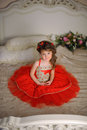 Small Dark-haired Girl In A Red Dress Stock Image - 63488521