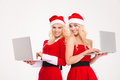 Beautiful Cheerful Blonde Sisters Twins Using Two Laptop Computers Stock Photo - 63541120