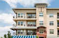 Three Story Condo Over Blue And White Awning Royalty Free Stock Photography - 63541897