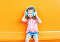 Happy Smiling Child Listens To Music In Headphones Over Colorful Orange Stock Photography - 63547512