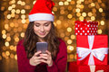 Pretty Cute Young Female In Santa Claus Hat Using Smartphone Stock Photos - 63549393