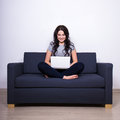 Pretty Woman Sitting On Sofa And Using Laptop At Home Stock Photo - 63611470