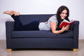 Happy Woman Lying On Sofa And Reading Book At Home Royalty Free Stock Photography - 63611497