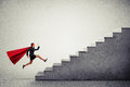 Superwoman In Red Cloar Running Up Stairs Royalty Free Stock Photo - 63700805