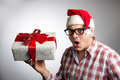 Funny Man In A Hat Santa With A Christmas Present In His Hand. Royalty Free Stock Images - 63736729